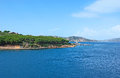 The porto faro picturesque view on with pinewood tiny lighthouse and rocky mountains on background palau sardinia Royalty Free Stock Images