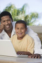 Porträt des vaters with his son auf laptop Lizenzfreie Stockbilder