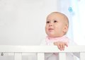 Portrait of an adorable baby standing in crib closeup Stock Image