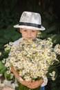 Portrait adorable boy in a hat with big white bouquet of camomiles. Royalty Free Stock Photo