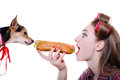 Portrait of adorable cute dog looking hungry at having fun eating a hot dog & happy smiling pinup beautiful funny blond girl