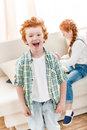 Portrait of adorable little boy laughing while little sister playing on sofa Royalty Free Stock Photo