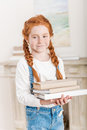Portrait of adorable little redhead girl holding pile of books Royalty Free Stock Photo