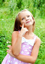 Portrait of adorable thinking little girl in summer day Royalty Free Stock Photo