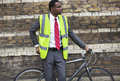 Portrait of african american businessman in safety vest with bicycle Royalty Free Stock Photos