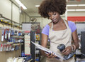 Portrait of an african american female store clerk standing at checkout counter scanning item Royalty Free Stock Image