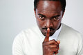 Portrait of african man with finger on lips over gray background Royalty Free Stock Photography