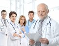 Portrait of aged doctor with medical residents Royalty Free Stock Photo
