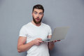 Portrait of amazed man holding laptop computer Royalty Free Stock Photo
