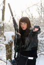 Portrait of armed nice young lady in winter forest Stock Images