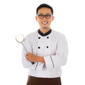 Portrait of asian chef holding spatula smiling and standing isolated on white background Stock Image