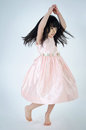 Portrait of asian cute gril is dancing on gray background Royalty Free Stock Images