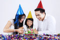 Portrait of asian family cutting a cake cheerful little girl birthday with her parents in birthday party Royalty Free Stock Photos