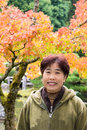 Portrait asian woman of beautiful middle aged smiling standing in front of maple tree in autumn colors vertical copy space Royalty Free Stock Image
