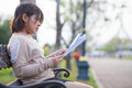 Portrait asian woman sitting reading a document on bench in the park Royalty Free Stock Images