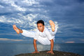 Portrait of Asian young man doing yoga on stone Royalty Free Stock Photo