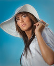 Portrait of attractive beautiful young woman in summer cap closeup against blue sky with white sun hat Stock Photography
