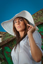 Portrait of attractive beautiful young woman in summer cap closeup against blue sky with white sun hat Royalty Free Stock Photo