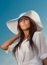 Portrait of attractive beautiful young woman in summer cap closeup against blue sky with white sun hat Royalty Free Stock Image