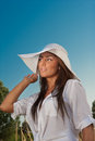 Portrait of attractive beautiful young woman in summer cap closeup against blue sky with white sun hat Stock Image