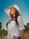 Portrait of attractive beautiful young woman in summer cap closeup against blue sky with white sun hat Stock Photos