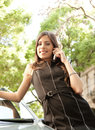 Portrait attractive businesswoman leaning car tree lined street having conversation her cell phone Royalty Free Stock Photo