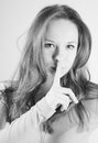 Portrait of attractive enigmatic girl with finger on lips black and white photo Stock Image