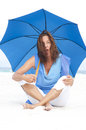 Portrait attractive funny mature woman sitting relaxed and happy with blue umbrella at beach isolated with ocean and bright white Royalty Free Stock Image