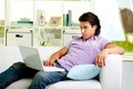 Portrait of attractive guy sitting with laptop at home Stock Image