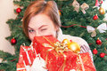 Portrait of attractive happy smiling girl holding christmas gifts gift boxes on tree background caucasian beautiful adult Royalty Free Stock Image