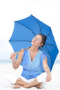 Portrait attractive mature woman sitting relaxed and happy with closed eyes and blue umbrella at beach isolated with ocean and Stock Photo