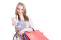 Portrait of attractive smiling girl with shopping bags showing t