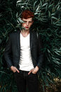Portrait of attractive stylish young guy model with red hair and freckles sitting on green grass, wearing jacket. Fashionable outd Royalty Free Stock Photo