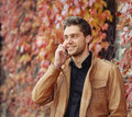 Portrait of attractive stylish young man speaking on the phone i beautiful in autumn park outdoors background Stock Image