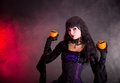 Portrait of attractive witch in purple gothic halloween costume holding jack o lantern style oranges Royalty Free Stock Photo