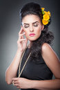 Portrait of a attractive woman with beads and flowers in her hair hairstyle make up beautiful female art yellow roses elegance Royalty Free Stock Photos