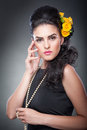 Portrait of a attractive woman with beautiful eyes beads and flowers in her hair hairstyle make up female art yellow roses Royalty Free Stock Image