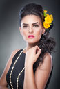 Portrait of a attractive woman with beautiful eyes beads and flowers in her hair hairstyle make up female art yellow roses Royalty Free Stock Photo