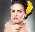 Portrait of a attractive woman with beautiful eyes and flowers in her hair hairstyle make up female art yellow roses elegance Stock Photo