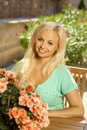 Portrait of attractive young blonde lady busty caucasian sitting in chair outdoors in a summer garden with flowers smiling Stock Photos