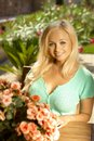 Portrait of attractive young blonde woman busty caucasian sitting outdoors in a summer garden with flowers smiling Royalty Free Stock Photography