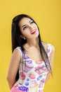 Portrait of attractive young brunette woman in pink tank top on yellow background. funny girl with dark hair Royalty Free Stock Photo