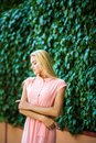 Portrait of attractive young sensual woman on a background of ivy wall with green leaves
