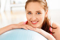 Portrait of attractive young woman relaxing fitness ball at gym smiling Stock Photo