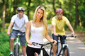 Portrait of attractive young woman on bicycle and two men behind