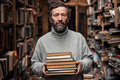 Portrait of authentic old man with beard and good eyes senior holding books in the hand on book market background Stock Photo