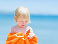 Portrait of baby wrapped in towel on beach Royalty Free Stock Photo