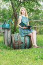 Portrait of barefoot student girl in garden with opened book summer Stock Photography