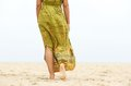 Portrait of a barefooted woman walking in the sand horizontal from behind Royalty Free Stock Photography
