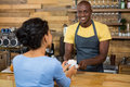 Portrait of barista serving coffee to customer in cafe Royalty Free Stock Photo